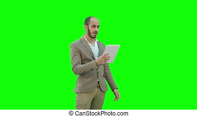 Young manager having video conference on tablet on a Green Screen, Chroma Key.