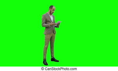 Young manager having video conference via tablet on a Green Screen, Chroma Key.