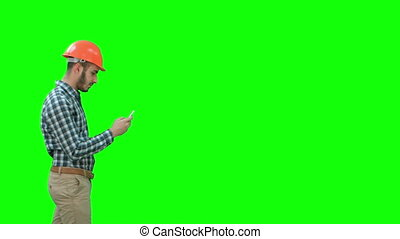 Young manager in helmet using mobile phone on a Green Screen, Chroma Key.