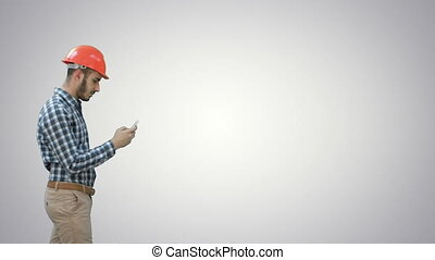Young manager in helmet using mobile phone on white background.