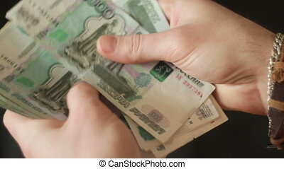 man's hand counts banknotes Russian rubles - young man's...
