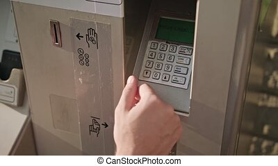 Young Man's Hand using ATM - A young man's hand using an...