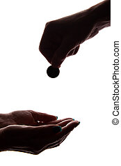 Young man's hand with a coin gives alms - silhouette, help