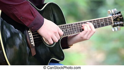 Young man's hands playing acoustic guitar artist musician outdoors