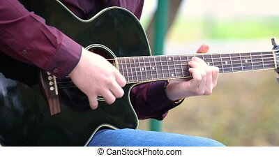 Young man's hands playing acoustic guitar artist musician...