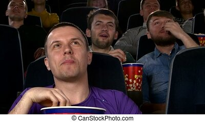 Young mans watching movie at cinema: comedy. Close up -...