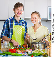Young married couple cooking vegetable dish in domestic ...