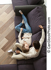 Young married couple in living room on couch