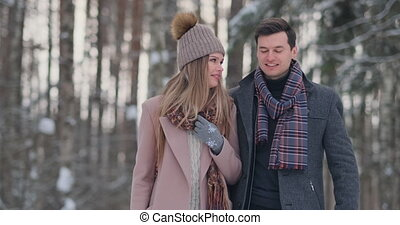 Young married couple in love walking in the winter forest. A...