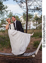 Young married couple is frivolous on a large swing, thereby...