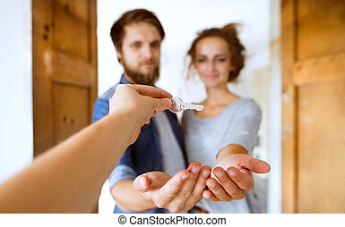 Young married couple with key in a new house. - Beautiful...