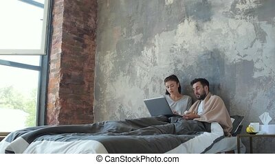 Young married couple working on laptop in bed