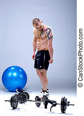 Young, masculine and fit man posing in front of weights