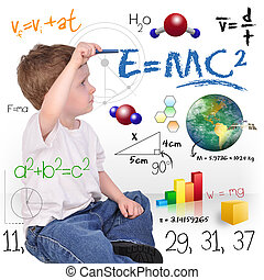 A young boy child is writing out math and science equations and formulas. He is sitting on the floor on a white background. Use it for a school, study or learning concept.