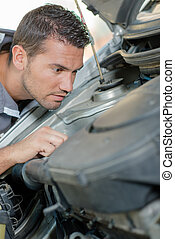 Young mechanic checking a car engine