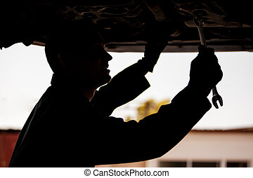 Silhouette of a young mechanic working an a suspended car at an auto shop