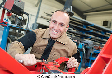 young mechanic fixing plow on the tractor