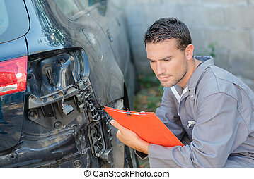 Young mechanic inspecting a damaged car