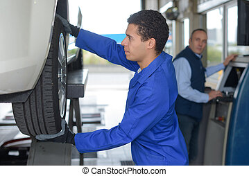 young mechanic inspecting the car wheel