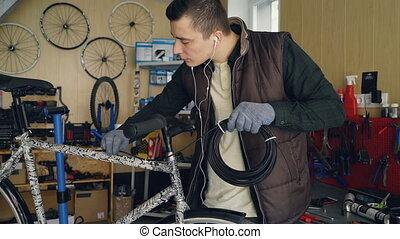 Young mechanic owner of bike repairing workshop is fixing...