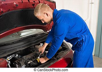 Young Mechanic Repairing Car