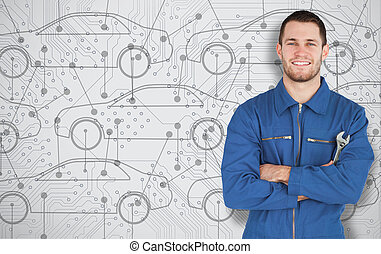 Young mechanic standing in front of cars background - Young...