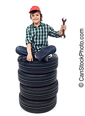 Young mechanic with tires and spanner