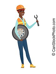 Young mechanic with tyre and spanner.
