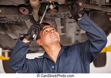 Young mechanic working on a car - Latin young mechanic...