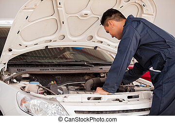 Young mechanic working on a engine - Young man in overall...