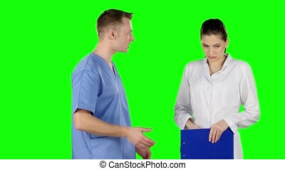 Young medical staff talking together. Doctor scolds intern. Green screen