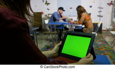 Young men and women in a workshop room with green screen tablet pc
