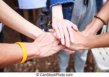 young men and women standing and stacking hands in a meeting on natural ground background at outdoor outing. Teamwork, diversity, collaboration, young generation, harmony, corporate culture concept