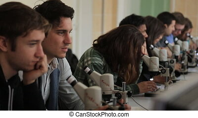 Young men and young women sit in a row in classroom with a microscope.