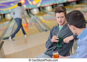 Young men chatting at the bowling alley