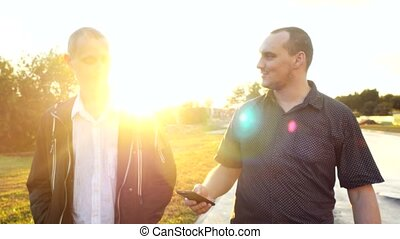 Young men have a serious talk while walking in the city during beautiful sunset with lense flare effects. Looking at mobile phone businessman showing something about new project, their work. 3840x2160