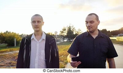 Young men have a serious talk while walking in the city in slow motion during beautiful sunset with amazing lense flare effects.