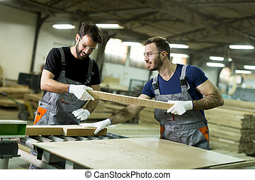 Young men in a furniture factory
