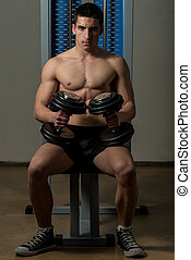 Young Men In Gym Exercising With Dumbbells