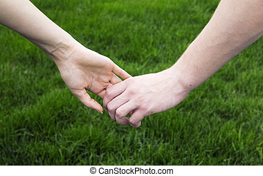 Young men keep woman hand on a background green grass