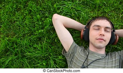 young men listen music in headphone lying on green grass,...