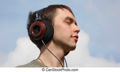 young men listen music in headphone on sky background