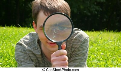 young men looks through a magnifying glass, looking to camera