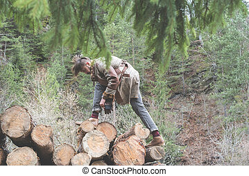 Young men on logs in the forest. Pine trees