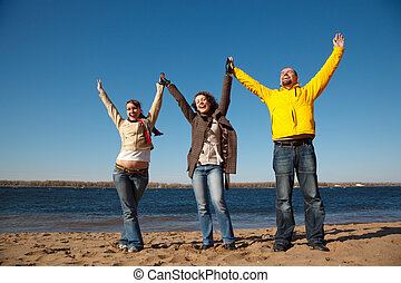 Young men on the nature have victoriously thrown up hands upwards. Productive leisure leads to success.