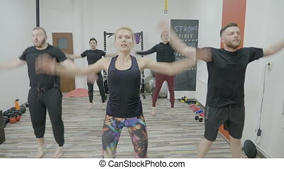 Young men on zumba class warming up by dancing in a gym studio led by a female instructor