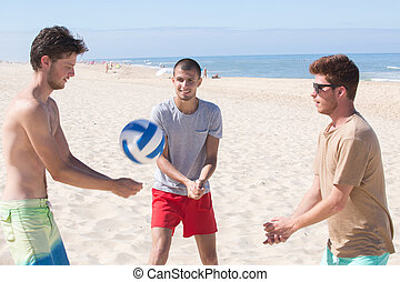 young men playing beach volleyball