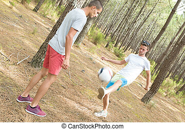 Young men playing football in forest