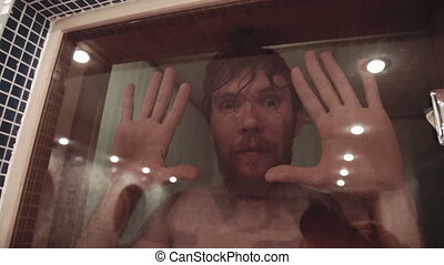 Young men relaxing in sauna Looks through the glass door with crickety eyes, jokes