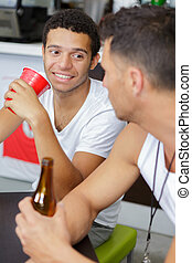 young men sat in bar having a drink